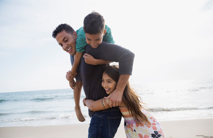 Dad playing on beach with two kids