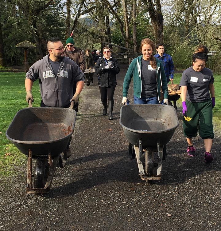 OCCU employees pushing wheelbarrows