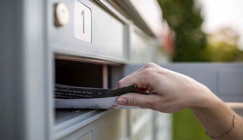Hand grabbing mail from mailbox