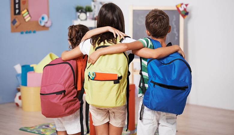 Kids with backpacks in a classroom