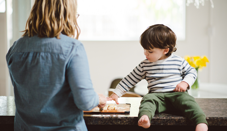 Young boy snacking on kitchen counter