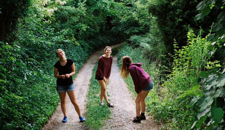 3 girls laughing on a dirt road