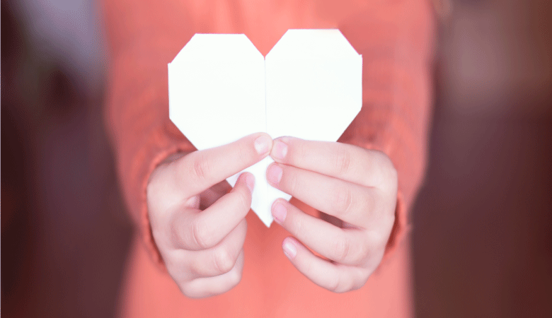 Person holding paper heart