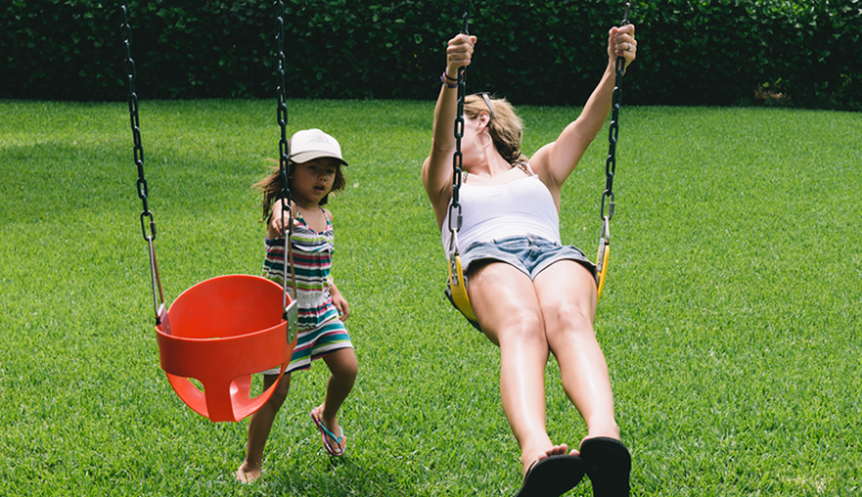 Mother and daughter playing on swings