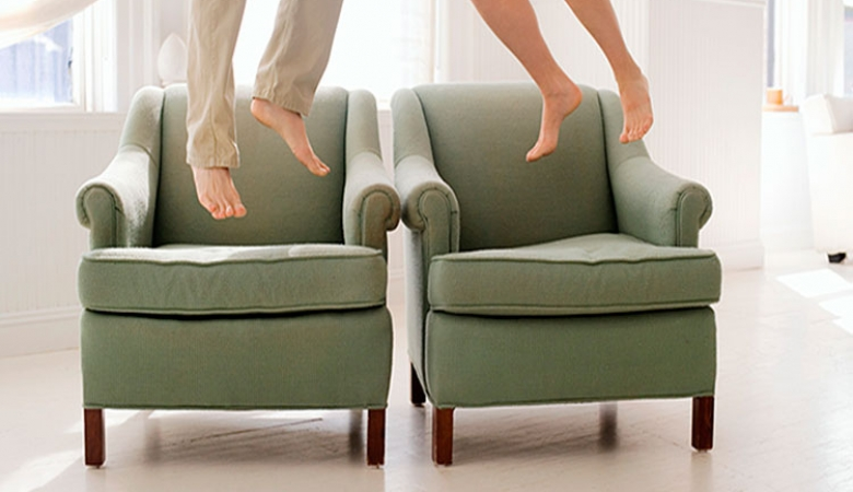 Couple jumping on arm chairs