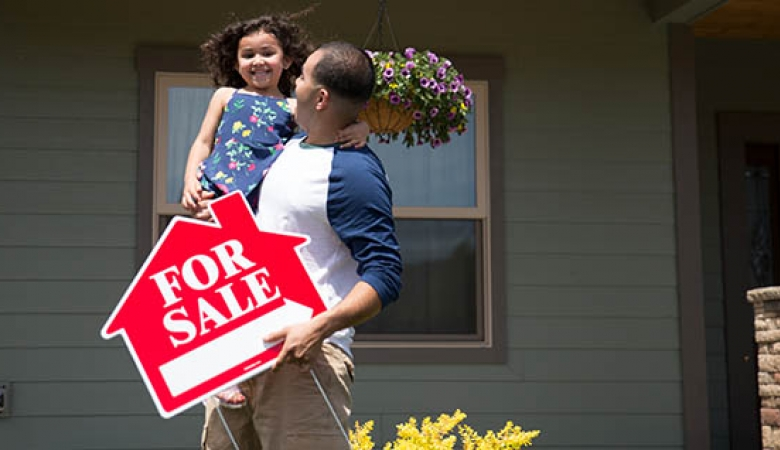 Father and daughter pulling for sale sign