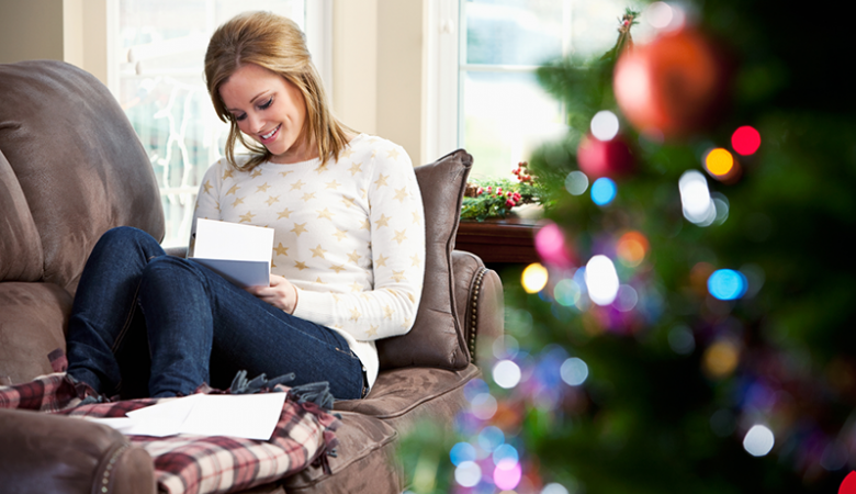Woman on couch working on Christmas list