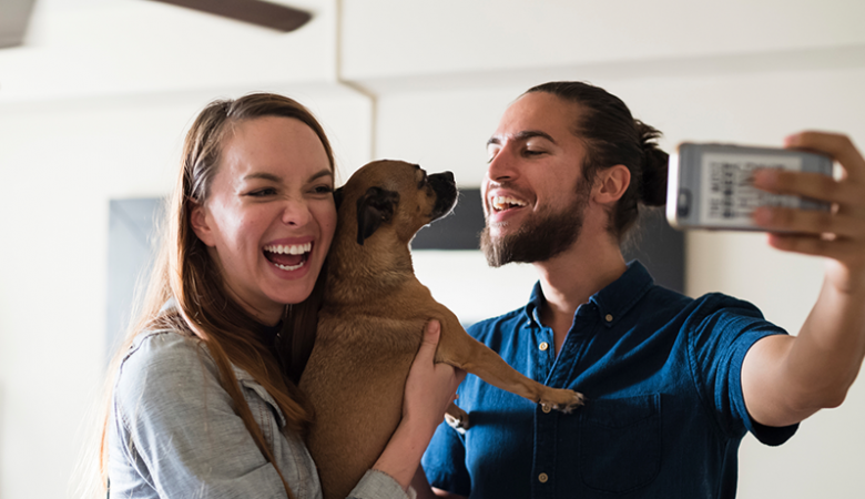 Couple taking a selfie with their dog in an apartment