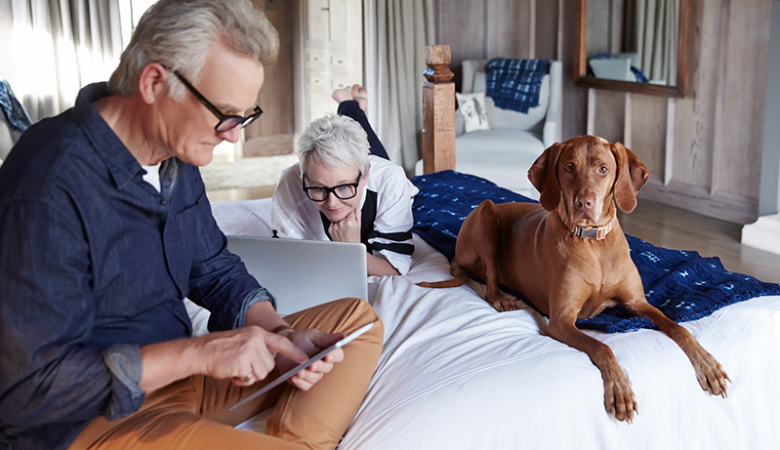 A man on a table and a woman on a laptop on the bed with their dog