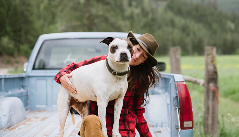 Woman with her dog in the back of a truck