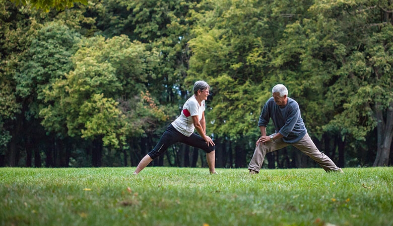 Retired couple stretching in the park