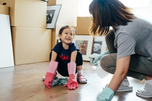 Little girl and mother cleaning new house