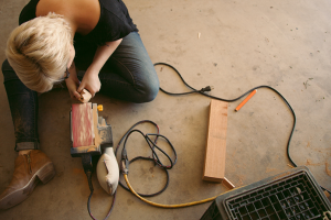 Woman sanding wood on the garage floor
