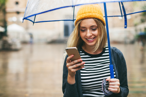Woman checking phone in the rain