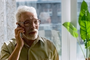 Man on phone in front of window