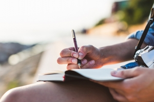 Woman writing in journal on sunny day