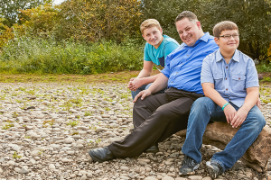Father and two sons on a log by the river