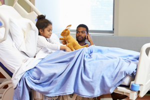 young girl in hospital bed with stuffed rabbit