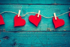Red hearts clipped to string on a blue wood background