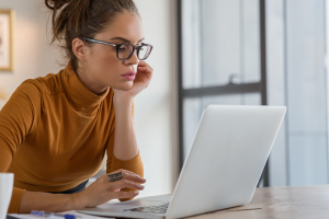 Woman in reviewing statements on laptop