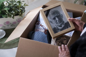 Person packing up a loved ones belongings and photos
