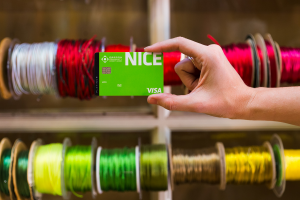 Hand holding OCCU Nice card in front of ribbon spools