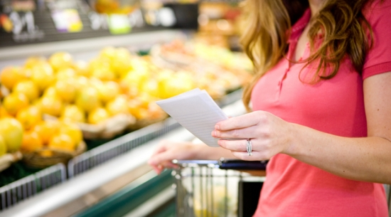 Woman in grocery store looking at shopping list