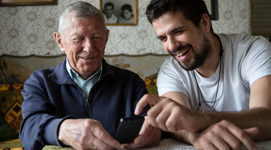 Elderly father and adult son looking at smartphone