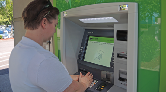 woman covering her hand while entering PIN at ATM