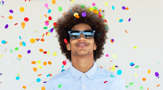 Man in sunglasses with confetti raining down