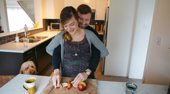 Couple in the kitchen eating an apple