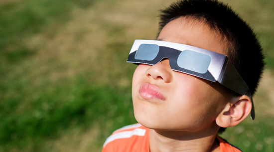 Boy watching the eclipse with glasses on