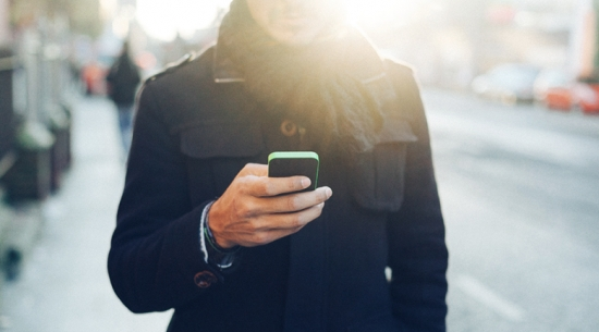 Man on smart phone in dark jacket
