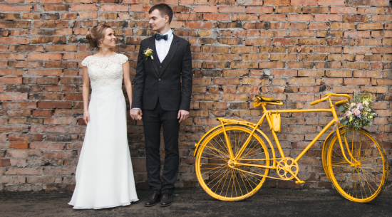 Couple posing for wedding photos with a yellow bike