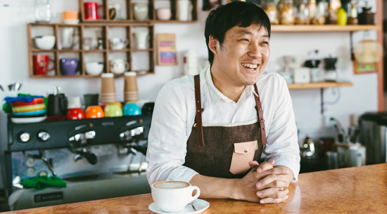 Asian man behind counter at his coffee shop