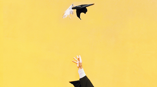 Hand throwing graduation cap into the air with a yellow background