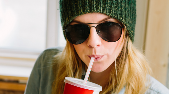 Young woman in sunglasses drinking a soda