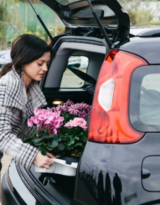 Woman loading flowers into vehicle
