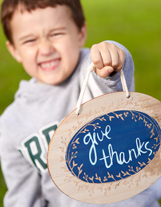 Boy holding give thanks sign