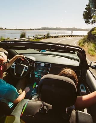 Two people in a convertible driving along a lake
